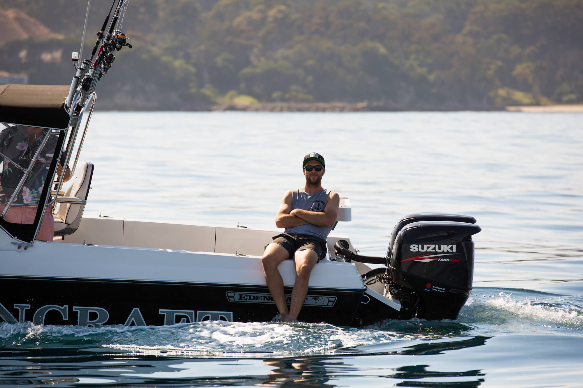 Man relaxes by sitting on the gunnel of an Edencraft 6.0m Offshore boat