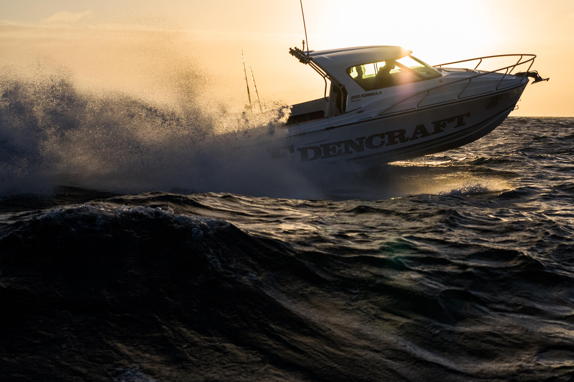 Edencraft 233 Formula Platinum travelling quickly offshore silhouetted against the sun