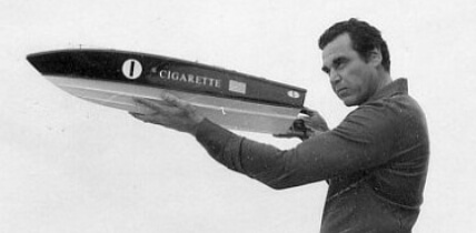 Don Aronow posing with a model of Cigarette boat